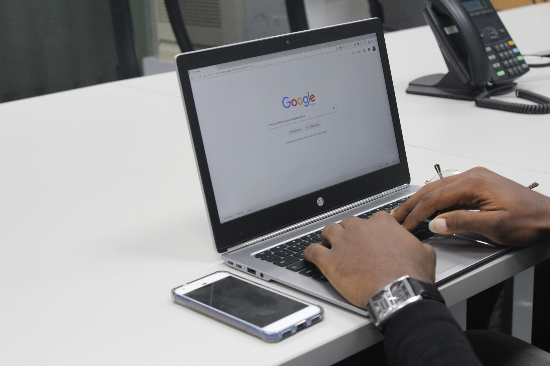 Man typing into a laptop and searching on Google