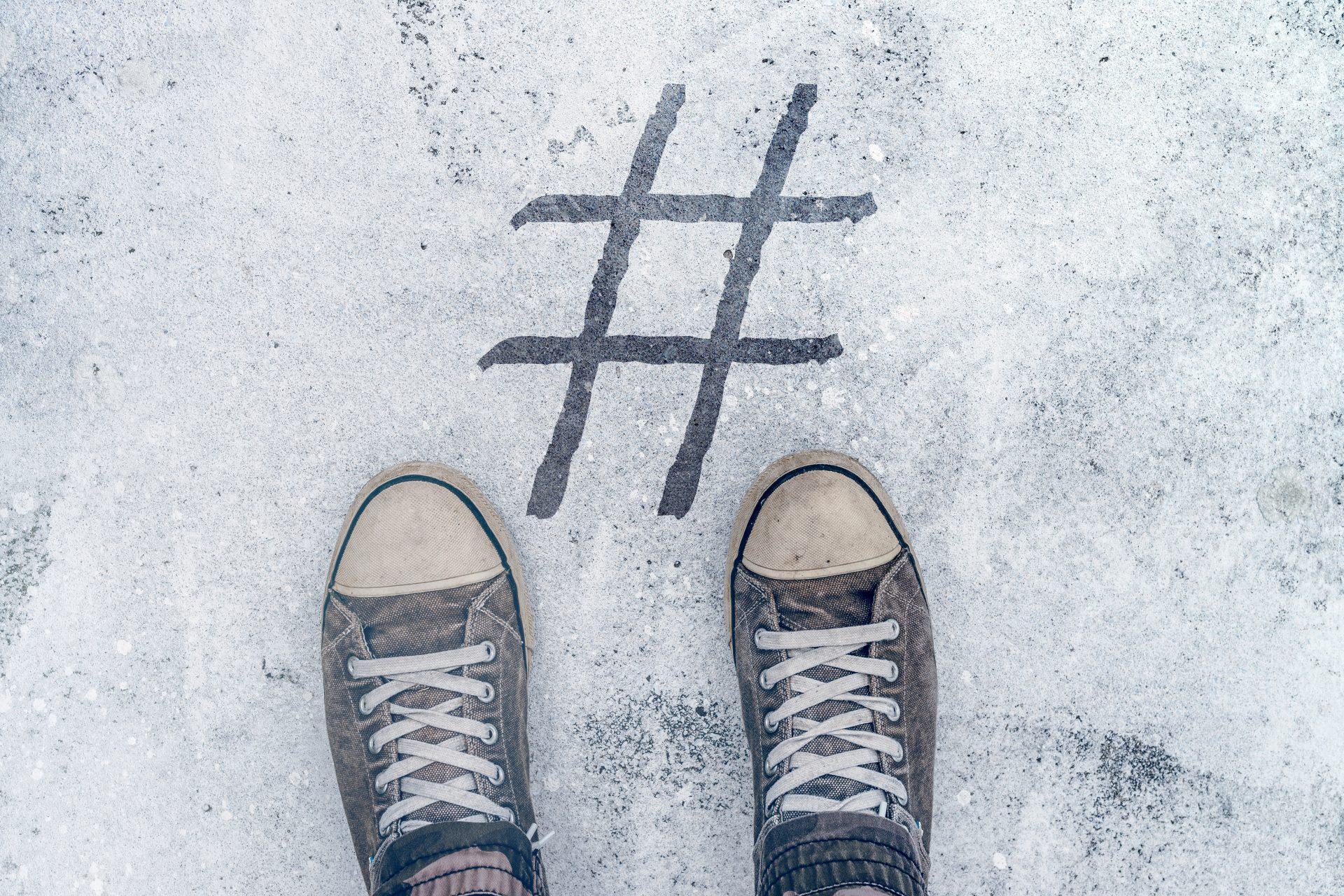 Feet standing over hashtag imprint on street