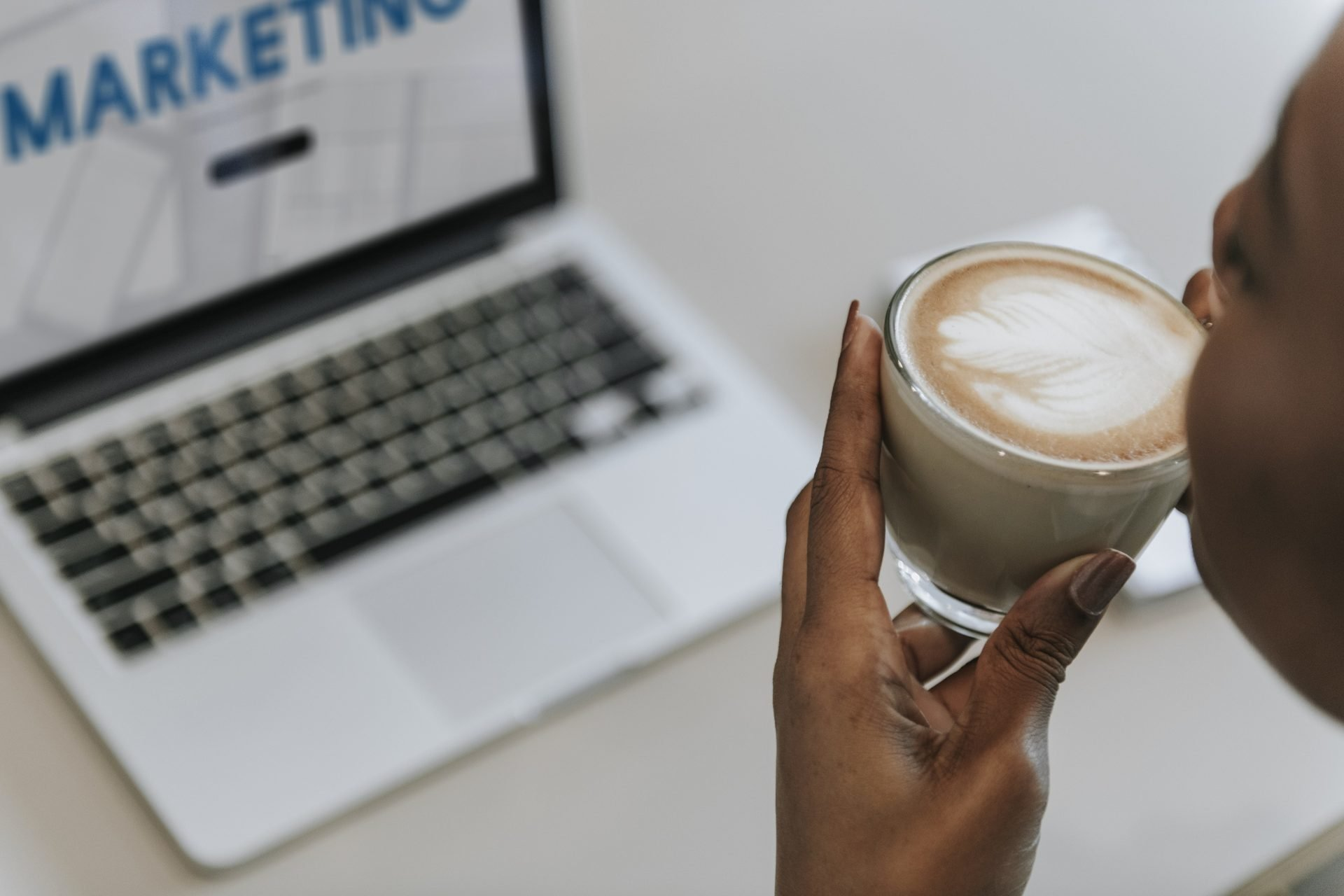 Woman sipping a cup of coffee while working
