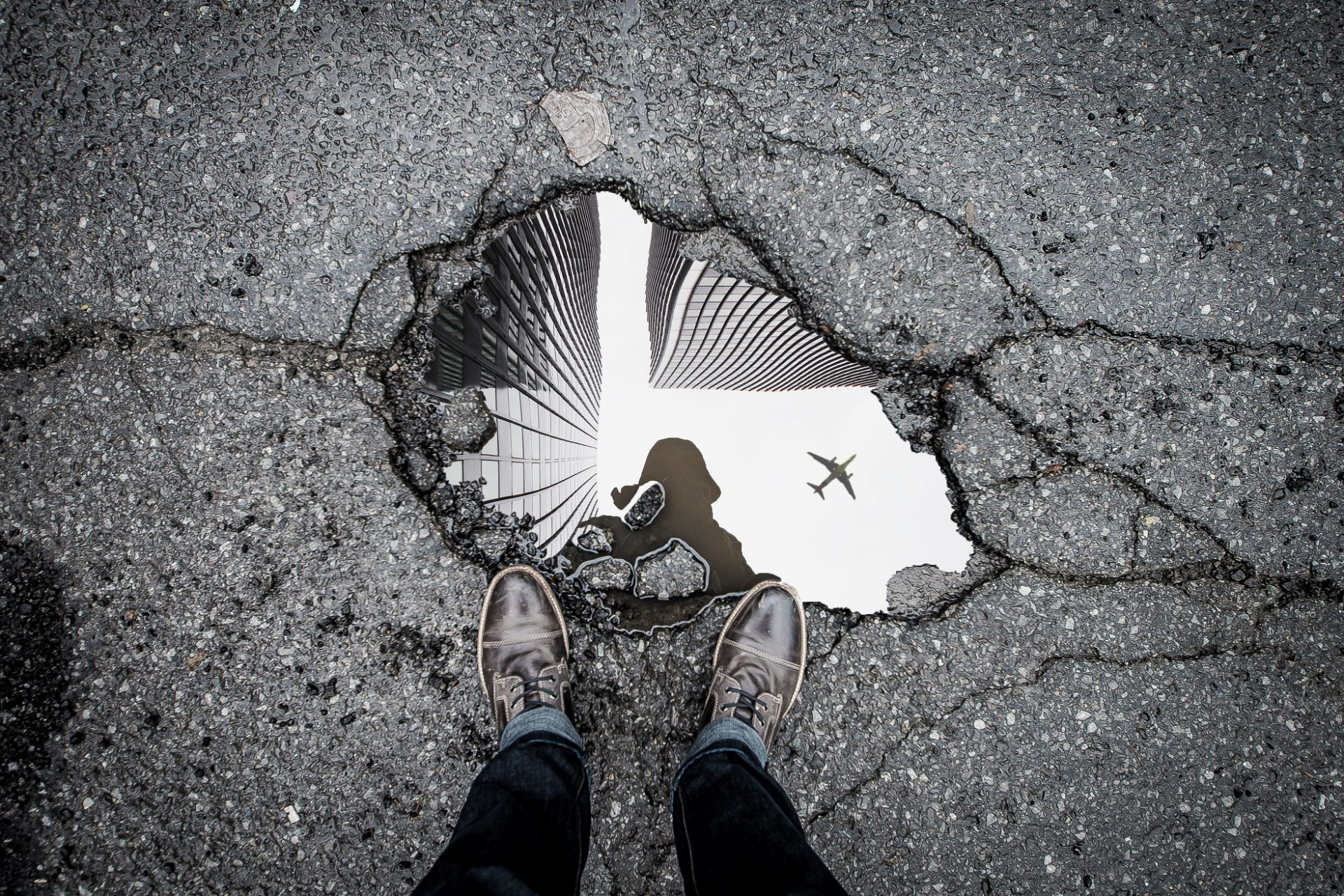 Man standing on the edge of a pothole taking a picture of the water which is reflecting the skyscape