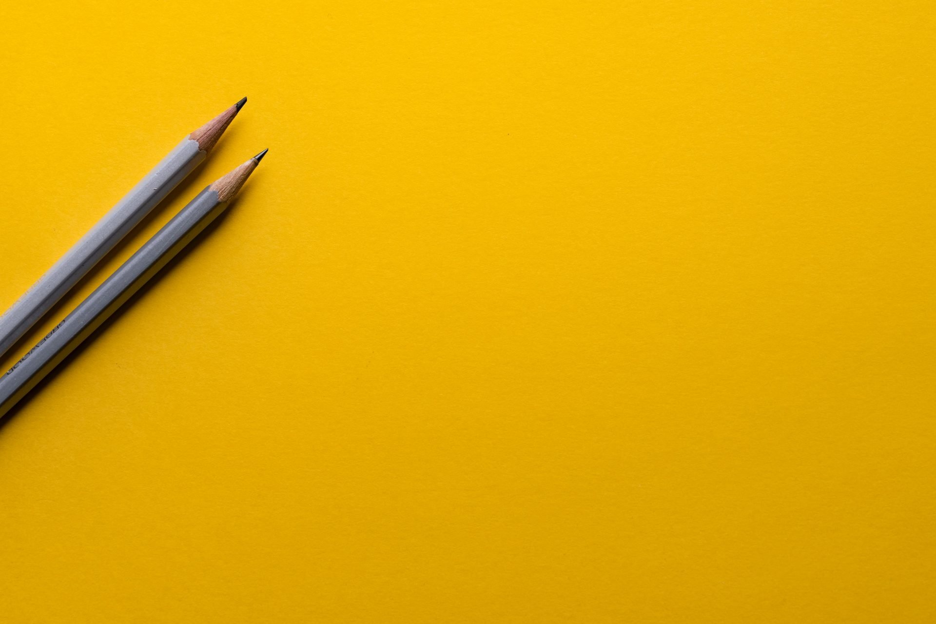 Two grey sharpened pencils on a yellow background