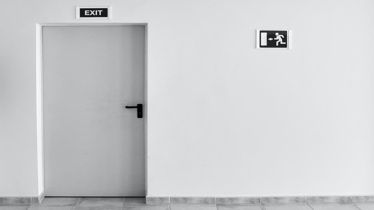 A grey tone wall and door with exit signs