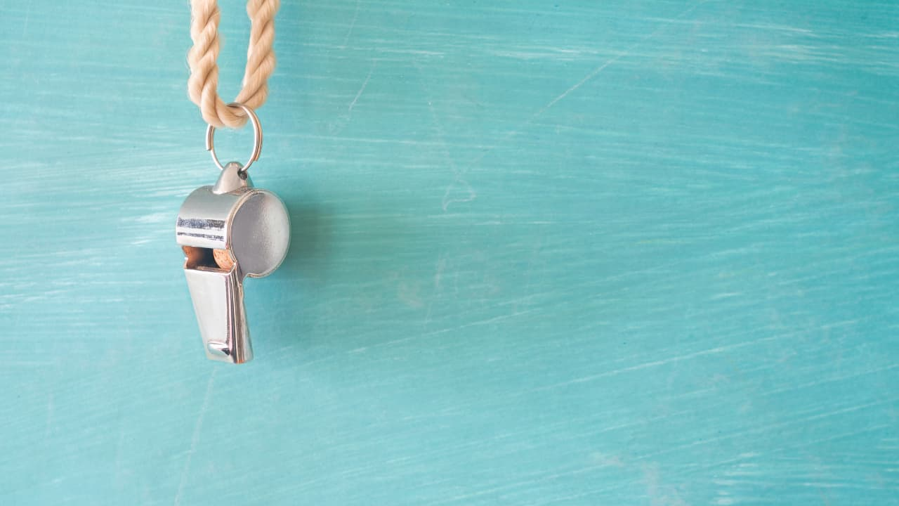 A whistle hanging on a light blue wall