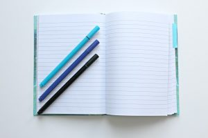 blue notebook with pens on a table